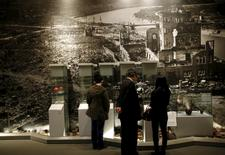 Visitors stand in front of a photograph showing Hiroshima city after the 1945 atomic bombing as they look at artifacts from the destruction caused by the bomb, at Hiroshima Peace Memorial Museum in Hiroshima, western Japan, March 26, 2015. REUTERS/Issei Kato