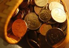 Рублевые монеты в Красноярске 12 января 2015 года. Рубль утром понедельника отбивает значительную часть глубоких потерь, понесенных в пятницу вечером после решения ЦБ повысить ставки валютного репо и за счет закрытия рискованных позиций под выходные. REUTERS/Ilya Naymushin