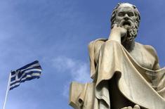 Una bandera nacional griega atrás de una estatua del filósofo Sócrates en Atenas . Imagen de archivo, 18 marzo, 2015.  Grecia negó el lunes un informe del diario Financial Times de que se preparaba para un incumplimiento de pagos si no alcanzaba un acuerdo con sus acreedores para fin de mes. REUTERS/Yannis Behrakis