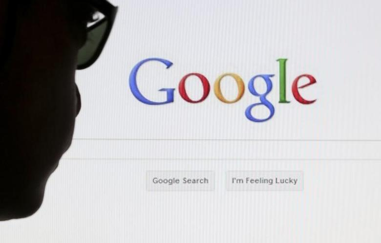 A computer user poses in front of a Google search page in this photo illustration taken in Brussels, May 30, 2014. REUTERS/Francois Lenoir
