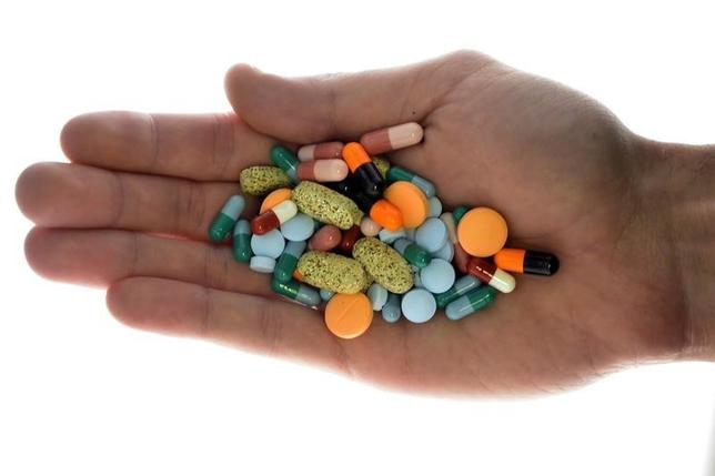 A person holds pharmaceutical tablets and capsules in this picture illustration taken in Ljubljana September 18, 2013.  REUTERS/Srdjan Zivulovic