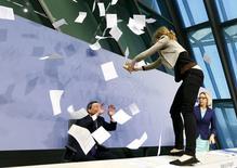 Una manifestante salta sobre el escritorio del presidente del Banco Central Europeo, Mario Draghi, durante una conferencia de prensa en Fráncfort, 15 abril, 2015. Una mujer que protestaba contra la política del Banco Central Europeo se subió el miércoles sobre el escritorio del presidente de la entidad, Mario Draghi, mientras éste ofrecía una rueda de prensa, interrumpiendo la habitualmente técnica presentación antes de que se la llevaran de la sala. REUTERS/Ralph Orlowski