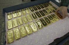 Слитки золота на заводе Красцветмет в Красноярске. 25 февраля 2013 года. Цены на золото растут, но завершат вторую подряд неделю снижением на фоне сомнений в сроке повышения процентных ставок ФРС. REUTERS/Ilya Naymushin