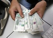 Сотрудник частной компании пересчитывает рублевые купюры в Красноярске 17 декабря 2014 года. Чистая прибыль второго по выручке российского продуктового ритейлера X5 Retail Group выросла в первом квартале 2015 года на 65,5 процента до 4,1 миллиарда рублей в годовом выражении, сообщила компания во вторник. REUTERS/Ilya Naymushin