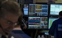 Трейдеры на фондовой бирже в Нью-Йорке. 17 апреля 2015 года. Фондовые рынки США завершили торги вторника разнонаправленно, при этом Nasdaq приблизился к абсолютному максимуму за счет возможного слияния двух биотехнологических компаний. REUTERS/Brendan McDermid