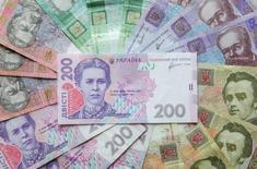 Украинские гривны в Киеве 6 августа 2014 года. Комитет по монетарной политике Национального банка Украины ожидает снижение рисков дестабилизации гривны, что позволит  начать смягчение монетарной политики, сообщила пресс-служба центрального банка. REUTERS/Konstantin Chernichkin