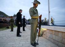 Australian Prime Minister Tony Abbott (L) pauses after laying a wreath during a dawn service at the ANZAC Commemorative Site in ANZAC Cove, Gallipoli, Turkey, in this April 25, 2015 handout courtesy of the Office of the Prime Minister.REUTERS/Brad Hunter/Office of the Prime Minister/Handout via Reuters