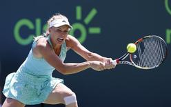 Caroline Wozniacki hits a backhand against Venus Williams (not pictured) on day eight of the Miami Open at Crandon Park Tennis Center. Williams won 6-3, 7-6 (1). Mandatory Credit: Geoff Burke-USA TODAY Sports