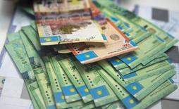 Банкноты тенге в отделении Евразийского банка в Алма-Ате. 15 января 2015 года. Бессменный президент Казахстана Нурсултан Назарбаев в понедельник опроверг вероятность девальвации тенге, которой ожидали инвесторы и международное рейтинговое агентство Fitch, предположившее обвал национальной валюты на 45 процентов. REUTERS/Shamil Zhumatov