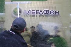 Мужчина моет окна в отделении Мегафона в Москве 28 ноября 2012 года. Чистая прибыль второго по доле рынка телекоммуникационного оператора России Мегафона в первом квартале 2015 года выросла в годовом выражении на 2,4 процента, а выручка снизилась на 1,2 процента, сообщила компания в среду. REUTERS/Sergei Karpukhin