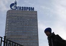 Женщина  проходит мимо штаб-квартиры Газпрома в Москве 24 февраля 2015 года. Крупнейший в мире производитель природного газа Газпром сократил в семь раз чистую прибыль по стандартам МСФО в 2014 году до 159 миллиардов рублей, сообщил концерн в среду. REUTERS/Maxim Zmeyev