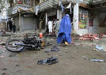 An Afghan woman walks at the site of a suicide attack in Jalalabad April 18, 2015. REUTERS/Parwiz