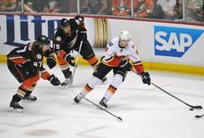 April 30, 2015; Anaheim, CA, USA; Calgary Flames center Joe Colborne (8) moves the puck against the defense of Anaheim Ducks defenseman Hampus Lindholm (47) and center Ryan Getzlaf (15) during the third period in game one of the second round of the 2015 Stanley Cup Playoffs at Honda Center. Mandatory Credit: Gary A. Vasquez-USA TODAY Sports