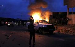 A protester throws stones at a burning car belonging to members of Burundi's police force who were detained by paramilitary officers, accused by civilians for shooting and killing a national military officer, during clashes between protesters and riot police in Burundi's capital Bujumbura April 30, 2015. REUTERS/Thomas Mukoya