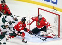 May 1, 2015; Chicago, IL, USA; Chicago Blackhawks goalie Corey Crawford (50) makes a save as defenseman Johnny Oduya (27) clears the puck away from Minnesota Wild center Mikael Granlund (64) and left wing Zach Parise (11) during the third period in game one of the second round of the 2015 Stanley Cup Playoffs at United Center. Mandatory Credit: Jerry Lai-USA TODAY Sports