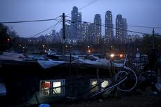 A man looks out from his shack as a luxury high-rise apartment complex is seen in the background at Guryong village in Seoul, South Korea, April 2, 2015. REUTERS/Kim Hong-Ji