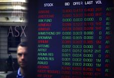 Pedestrians are reflected in the window of the Australian Securities Exchange next to a board displaying stock prices in central Sydney September 24, 2014.  REUTERS/David Gray