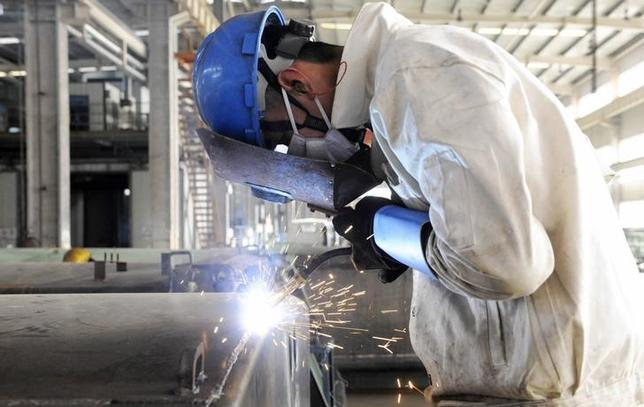 An employee welds the exterior of a vehicle along a production line at a factory in Qingdao, Shandong province December 1, 2014. REUTERS/China Daily