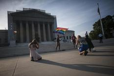 A demonstrator (back) waves a flag while awaiting decisions in two cases regarding same-sex marriage at the U.S. Supreme Court in Washington, June 26, 2013. REUTERS/James Lawler Duggan
