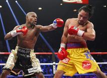 Floyd Mayweather, Jr. of the U.S. lands a left to the face of Manny Pacquiao of the Philippines (R) in the 11th round during their welterweight WBO, WBC and WBA (Super) title fight in Las Vegas, Nevada, May 2, 2015.    REUTERS/Steve Marcus -