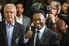 Soccer legends Pele (R) and Franz Beckenbauer pose for photographs after they ceremonially turned on the lights of the Empire State Building during an event to celebrate the start of the New York Cosmos 2015 season, in New York April 17, 2015. REUTERS/Lucas Jackson