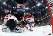 Austria's goaltender Bernhard Starkbaum fails to save a goal of Canada's Nathan MacKinnon during their Ice Hockey World Championship game at O2 arena in Prague, Czech Republic May 12, 2015. REUTERS/Martin Rose/Pool