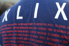 A fan wearing a souvenir t-shirt from Super Bowl XLIX and listing New England Patriots players including quarterback Tom Brady waits in line to hear Brady speak at Salem State University in Salem, Massachusetts, United States May 7, 2015.  REUTERS/Brian Snyder - RTX1C136