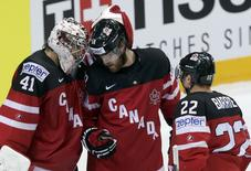 Canada's goaltender Mike Smith (L) celebrates with his teammates David Savard and Tyson Barrie (R) after defeating Belarus during their Ice Hockey World Championship quarterfinal game at the O2 arena in Prague, Czech Republic May 14, 2015.    REUTERS/David W Cerny