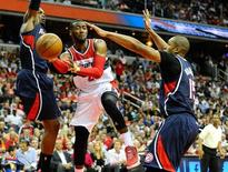 May 15, 2015; Washington, DC, USA; Washington Wizards guard John Wall (2) passes as Atlanta Hawks forward Paul Millsap (4) and center Al Horford (15) defend during the second half in game six of the second round of the NBA Playoffs at Verizon Center. Mandatory Credit: Brad Mills-USA TODAY Sports