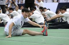 Chinese hurdler Liu Xiang (front) stretches with students at a school as part of the launching event of Laureus World Sports Awards, in Shanghai, June 9, 2014. REUTERS/Stringer