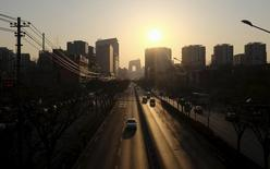 Apartment blocks (R) are seen at sunset in Beijing, April 7, 2015. REUTERS/Jason Lee