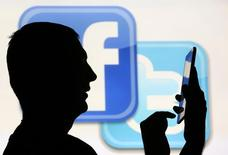 A man is silhouetted as he uses a mini tablet computer while standing in front of a video screen with the Facebook and Twitter logos, in this picture illustration taken in Sarajevo October22, 2013.  REUTERS/Dado Ruvic