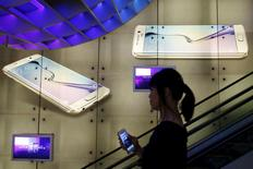 A woman holding an Apple iPhone passes a Samsung Galaxy S6 advertisement at a mall in Singapore April 24, 2015. Samsung is expected to announce Q1 results this week. Picture taken April 24, 2015.  REUTERS/Edgar Su
