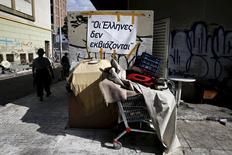 """El ministro de Trabajo griego dijo el martes que Atenas alcanzará pronto un acuerdo con sus acreedores internacionales que podría desbloquear más préstamos para el país con problemas de liquidez. En la imagen, las pertenencias de un indigente junto a un cartel que dice """"Los griegos no pueden ser chantajeados"""" en la ciudad portuaria de El Pireo, cerca de Atenas. 19 mayo 2015. REUTERS/Alkis Konstantinidis"""