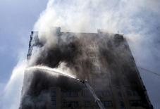 Охваченный огнем многоэтажный дом в Баку. 19 мая 2015 года. Число жертв пожара в 16-этажке в столице Азербайджана достигло к среде 15, сообщили власти, задержавшие главу компании, ответственной за облицовку строения. REUTERS/Ehtiram Jabi