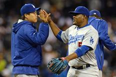 Los Angeles Dodgers third baseman Juan Uribe (5) and starting pitcher Hyun-Jin Ryu (99) high-five after the Dodgers beat the San Diego Padres 3-0 at Petco Park; Apr 24, 2015; San Diego, CA, USA; Jake Roth-USA TODAY Sports