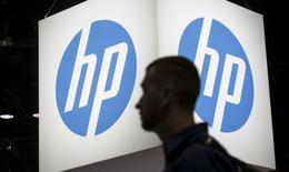 Un asistente a la conferencia de Microsoft Ignite technology pasea junto al logo de Hewlett-Packard (HP) en Chicago, Illinois, el 4 de mayo de 2015. Hewlett-Packard Co, que está en un proceso de división, pronosticó menores costos relativos a la separación que las expectativas de muchos analistas y reportó el jueves una ganancia trimestral por encima de las estimaciones del mercado. REUTERS/Jim Young