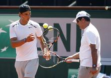 Rafael Nadal of Spain and his coach Toni Nadal (R) attend a training session for the French Open tennis tournament at the Roland Garros stadium in Paris, France, May 22, 2015.  REUTERS/Vincent Kessler