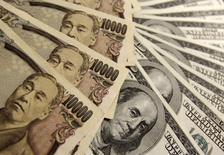 Купюры валют доллар США и иена в Токио 27 ноября 2009 года. Курс доллара к иене поднялся до двухмесячного максимума после публикации отчета об инфляции в США, превзошедшего прогнозы аналитиков. REUTERS/Yuriko Nakao