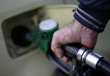 Мужчина заправляет автомобиль на АЗС в Риме. 6 января 2015 года. Цены на нефть растут после значительного падения накануне, так как аналитики предполагают, что запасы нефти в США снизились четвертую неделю подряд. REUTERS/Max Rossi