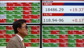 Un peatón camina junto a un tablero electrónico que muestra el índice Nikkei de Japón (arriba a la derecha) y la tasa cambiaria entre el yen japonés y el dólar estadounidense, afuera de una agencia de la bolsa, en Tokyo, 24 de febrero de 2015. Un índice de las acciones en Asia caía el jueves por un declive de los mercados de China continental, Hong Kong y Australia, y el dólar escaló a su nivel más alto frente al yen desde el 2002 por las expectativas de que la Reserva Federal de Estados Unidos subirá las tasas de interés este año. REUTERS/Yuya Shino
