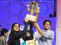 Vanya Shivashankar (L) of Olathe, Kansas, and Gokul Venkatachalam, St. Louis Missouri lift the trophy after becoming co-champions after the final round of the 88th annual Scripps National Spelling Bee at National Harbor, Maryland May 28, 2015.      REUTERS/Joshua Roberts