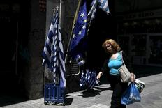 A woman carrying bags of goods makes her way past Greek national flags and European Union flags on display in Athens May 25, 2015. REUTERS/Alkis Konstantinidis