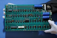 En la fotografía de archivo, un empleado sostiene una computadora personal Apple-1 antes de su subasta en la casa Christie's en Londres.  28 de agosto de 2012.  Un cheque de 100.000 dólares está esperando a una misteriosa mujer que donó una computadora Apple 1 a una compañía de reciclaje de Silicon Valley. REUTERS/Stefan Wermuth