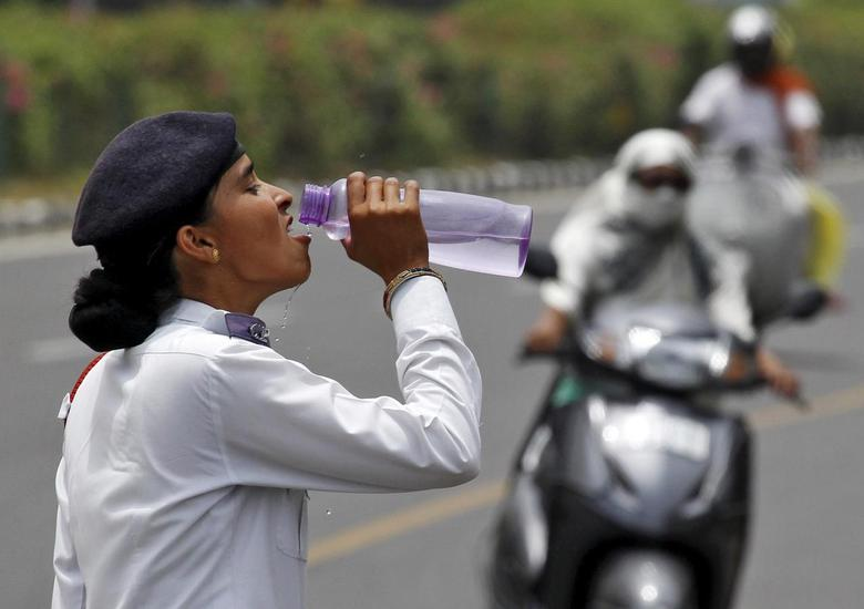 A traffic police woman drinks water as commuters drive along a road on a hot summer day in Chandigarh, India, May 31, 2015  REUTERS/Ajay Verma