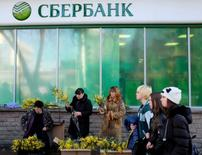 Girls walk past vendors selling bunches of mimosa flowers near a branch of Sberbank in Stavropol March 6, 2015. REUTERS/Eduard Korniyenko (RUSSIA - Tags: BUSINESS) - RTR4SD6V