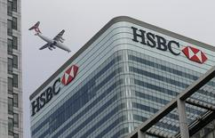 A Swiss International aircraft flies past the HSBC headquarters building in the Canary Wharf financial district in east London February 15, 2015.  REUTERS/Peter Nicholls
