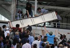 Espectadores removem estrutura de metal que caiu do placar da quadra Philippe Chartier, durante partida do Aberto da França, no complexo de Roland Garros, em Paris. 02/06/2015 REUTERS/Pascal Rossignol