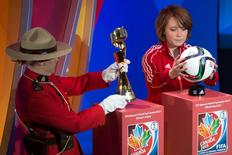 A member of the Royal Canadian Mounted Police carries the FIFA Women's World Cup trophy along with West Ottawa Soccer Club player Talia Laroche, who carries the official match ball, as part of the preliminary activities surrounding the official draw for the FIFA Women's World Cup Canada 2015 in Gatineau, Quebec December 6, 2014. Mandatory Credit: Marc DesRosiers-USA TODAY Sports