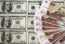 Рублевые и долларовые купюры в Сараево 9 марта 2015 года. Евро достиг отметки 60,18 рубля на Московской бирже впервые с 7 апреля, а доллар - 54,02 впервые с 21 апреля во время волатильной торговли по ходу выступления главы ЕЦБ Марио Драги. REUTERS/Dado Ruvic